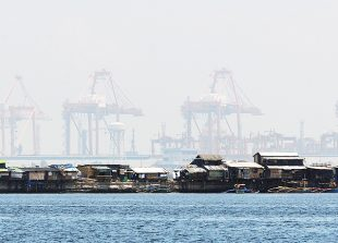A row of shanty dwellings are dwarfed by giant cranes at the south harbour cargo terminal in Manila on July 13, 2016. The Philippines' economy grew a better-than-expected 6.9 percent in the first quarter, the government said May 19, putting it on track to meet full year targets and making it one of Asia's best performers for the three month period. / AFP PHOTO / TED ALJIBE