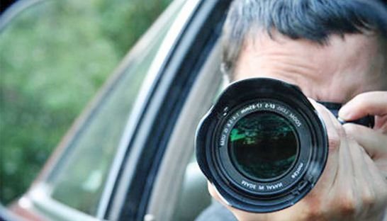 a-representative-image-of-a-private-investigator-photographing-his-subject-from-a-car-supplied
