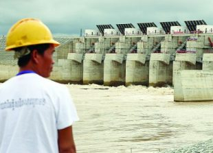 business_a_worker_stands_in_front_of_the_lower_sesan_ii_dam_as_it_was_went_inline_in_september_in_stung_treng_province_25_09_2017_hong_menea