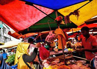 A Malaysian woman (C) shops at a wet market in downtown Kuala Lumpur on January 18, 2018.  / AFP PHOTO / MANAN VATSYAYANA